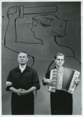 Singer and composer Mieczysław Fogg (visible on the left) with a red and white armband, during an occasional performance at the Polish Theater (the Mermaid of Warsaw is visible in the background on the stage), Poznań 20.10.1956. Photo: Archive of Michał Fogg